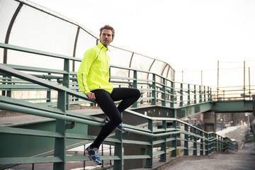 Male runner sitting on a hand rail