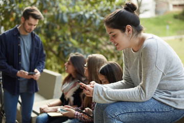 Mixed group of relaxed young people with phones