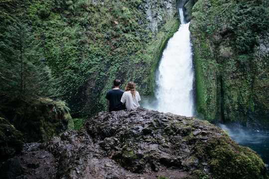Man and woman sitting on a rock in front of a waterfall