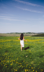 Long hair woman walking on the green grass hill in summer