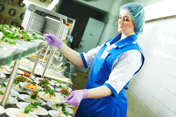 buffet female worker servicing food in cafeteria