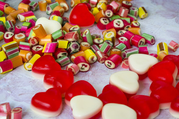 Scattered colorful sweetmeats and red white candied fruit jelly close up