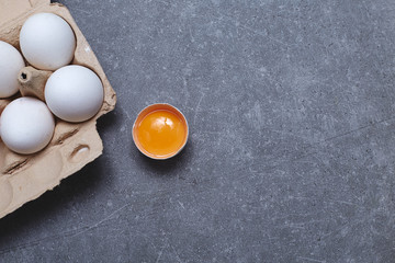 Eggs in a cardboard box with egg yolk on a grey stone kitchen table. Top view. Space for text.