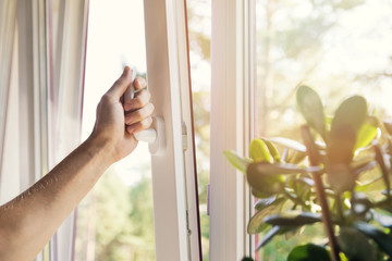 hand open white plastic pvc window at home