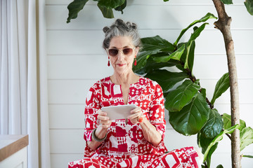 Stylish senior woman texting on mobile phone in her house