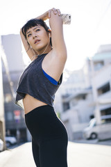 Fit Asian woman stretching before running