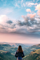 Hiker overlooking a scenic mountainous valley at sunset