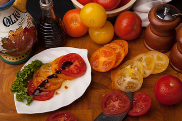 Sliced tomatoes on leaf plate with whole and sliced tomatoes, knife,  olive oil