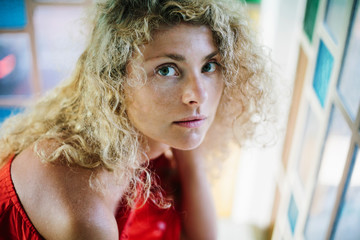 Portrait of beautiful young woman with Curly long hair style  near the window. Pensive face close up
