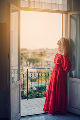 Portrait of beautiful young woman with Curly long hair style in long red dress staying near balcony, enjoy sunny day in Europe travel