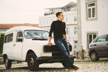 Young handsome man staying on the hood of  vintage car in European city