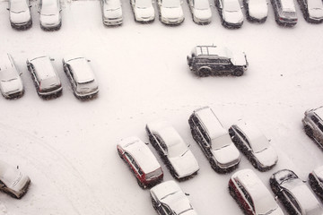Cars in the parking lot in heavy snow. Snowfall, weather conditions, transportation