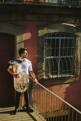 Young musician man with tuba musical instrument. staying near house. European street, sunny summer day