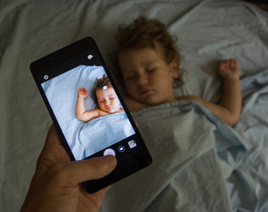 Photoshot of happy mother taking photo her baby boy in bed with smart phone at home. focused on the device