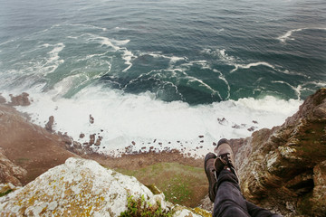 Traveler girl feet above cliff precipice and Atlantic ocean. Freedom, beautiful sea landscape