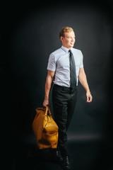 Traveling businessman with yellow bag. Studio portrait, black background