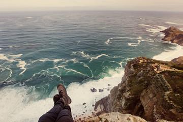 Traveler woman feet above cliff precipice and Atlantic ocean, South Africa