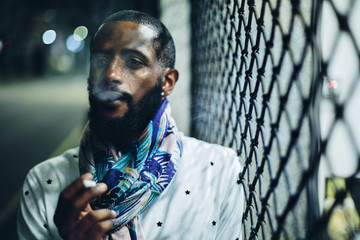 Portrait of smoking man with cigarette outdoor. Mixed race black skin and beard