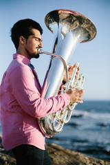Outdoor Portrait of musician with tuba wind musical instrument. Atlantic Ocean beach