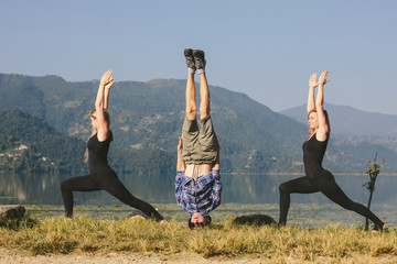 Young yogis doing yoga headstand and standing asana. Beautiful mountain lake landscape background. Complex amazing and funny yoga picture