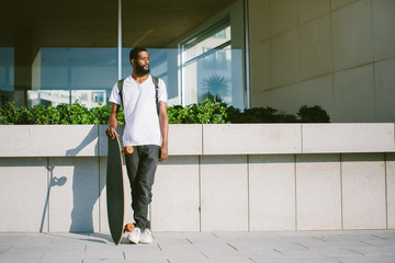 Portrait of man with skate board outdoor. Mixed race black skin and beard. Summer sport activity