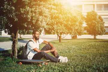 Portrait of man with skate board on the meadow. Mixed race black skin and beard. Summer sport activity outdoor