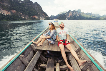 Young couple travel on boat on tropical mountain lake