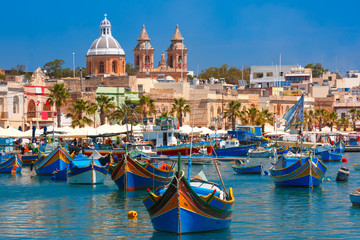 Traditional eyed colorful boats Luzzu in the Harbor of Mediterranean fishing village Marsaxlokk, Malta
