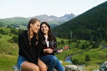 Women playing ukulele in nature