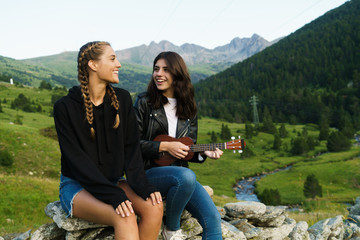 Women playing ukulele in nature