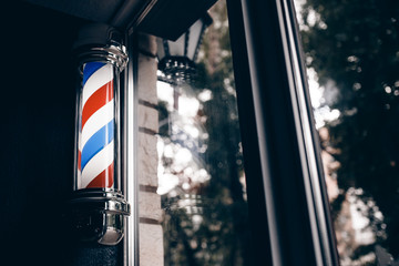 Barber shop pole at entrance of the window. background is dark. copyspace