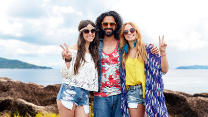 happy hippie friends showing peace on summer beach