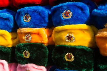 Rows of russian winter hats of different colors with army emblems at the street market at Old Arbat street, iconic popular souvenir from Russia.