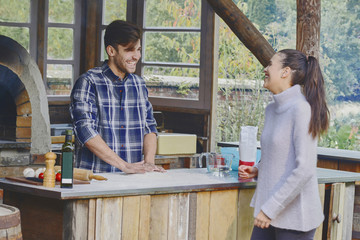 Young couple cooking in outdoor kitchen together.