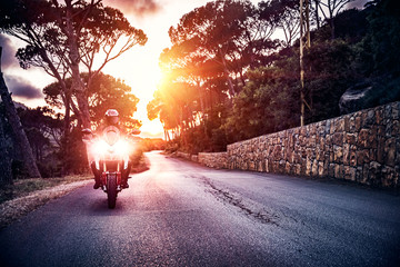Fototapete - Motorcyclist in sunset light