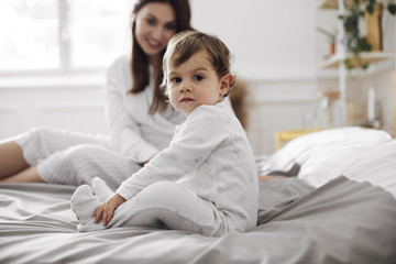 Portrait of baby boy sitting with mother on bed at home