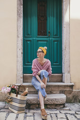 Thoughtful woman looking away while sitting against door