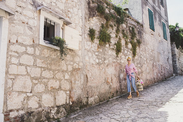 Woman walking on footpath by wall