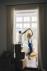 Couple dancing in new house seen through doorway