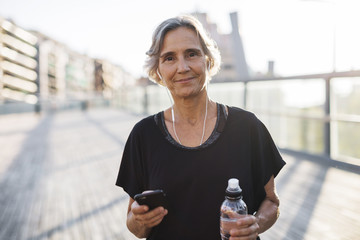 Portrait of confident woman holding smart phone and water bottle at bridge