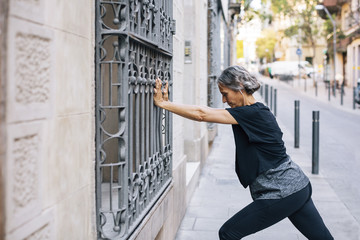 Side view of woman stretching against window railing on footpath
