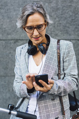 Woman in jacket using smart phone while standing against wall