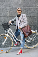 Portrait of confident woman with bicycle against wall on footpath