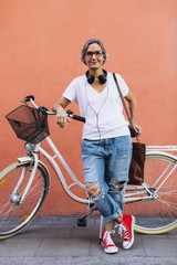 Portrait of confident woman with bicycle standing against wall