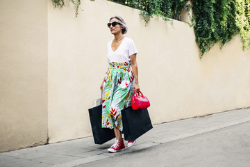 Fashionable woman walking on footpath with bags against wall