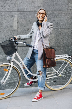 Happy woman talking on smart phone with bicycle against wall on footpath