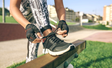 Low section of woman tying shoelaces while exercising at park
