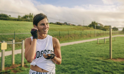 Happy woman listening music while exercising at park