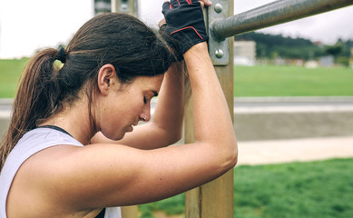 Tired woman leaning against gymnastics bar at park