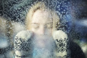 Close-up of woman with eyes closed seen through glass during winter